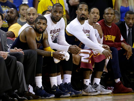 Cleveland Cavaliers' Kyrie Irving, from second from left, LeBron James, J.R. Smith and teammates sit on the bench during the second half of Game 2 of basketball's NBA Finals against the Golden State Warriors in Oakland, Calif., Sunday, June 5, 2016. (AP Photo/Marcio Jose Sanchez)