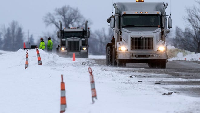 Trucks haul contaminated soil and snow away from the site of a diesel fuel spill Thursday, Jan. 26, 2017, after a pipeline owned by Magellan Midstream Partners broke at about 8 a.m. near Hanlontown, IA.