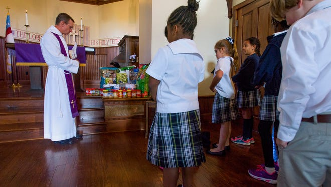 Holy Cross Episcopal School students take part, along with Rev. Robert Wisnewski, in the blessing of the food and socks they have collected for senior citizens and dogs at their school chapel in Montgomery, Ala. on Wednesday December 9, 2015. The collected items are for Meals on Wheels through the Montgomery Area Council on Aging program.