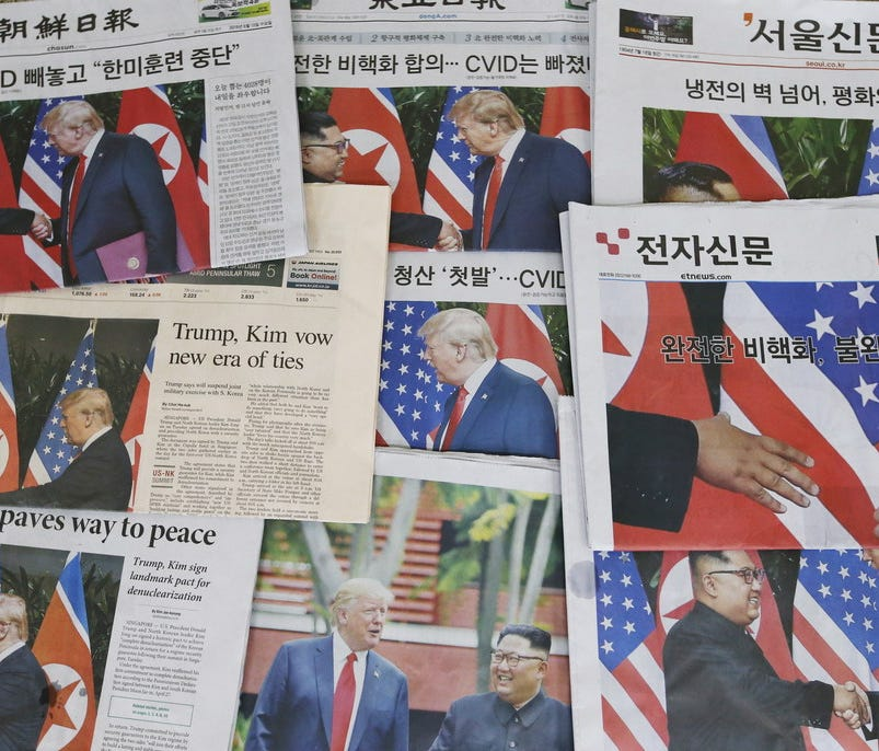 Newspaper front pages show President Trump and North Korean leader Kim Jong Un during their meeting in Singapore on June 12, 2018.