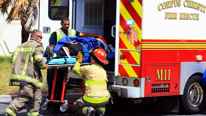 Corpus Christi firefighters transfer a man in an ambulance on Sept. 24, 2016, on the corner of Ennis Joslin and South Padre Island Drive in Corpus Christi.
