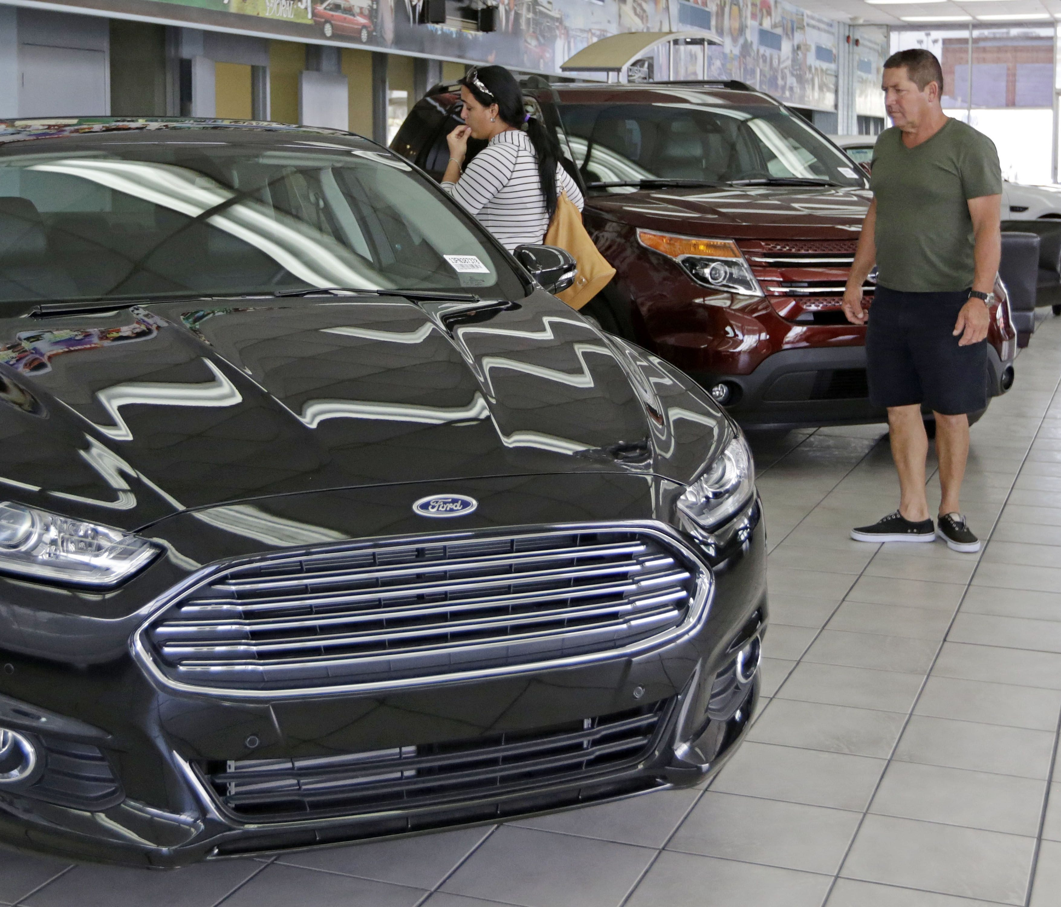 Orestes Perez and his niece Yanuska Perez look at a 2013 Ford Fusion SE at a dealership in Hialeah, Fla. Aug. 21, 2014.