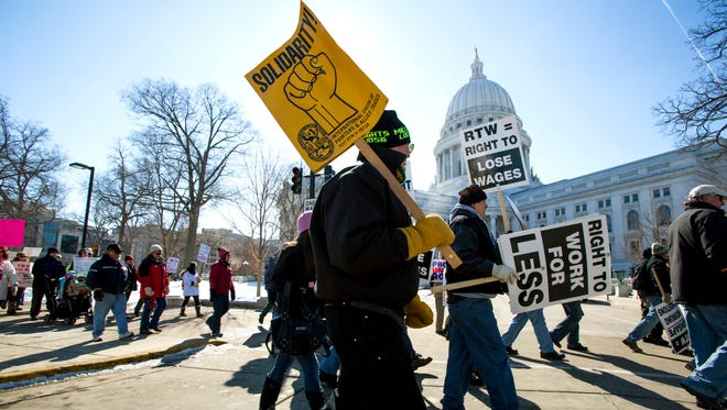 "Protesters march around the state Capitol in Madison after participating in a rally against a ""right-to-work"" proposal on Saturday."