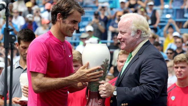 John F. Barrett, right, chairman of the board, president and CEO, Western & Southern Financial Group gives Roger Federer his Rookwood Pottery trophy after Federer won the Western & Southern Open finals.