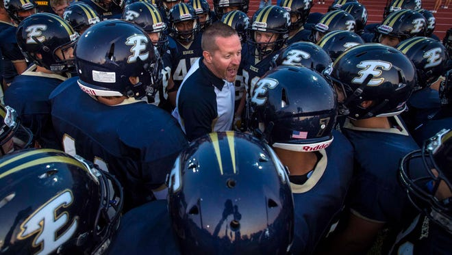 Essex head coach Charlie Burnett huddles with his team before the first game of the season against Colchester in Essex Junction on Friday, August 28, 2015.
