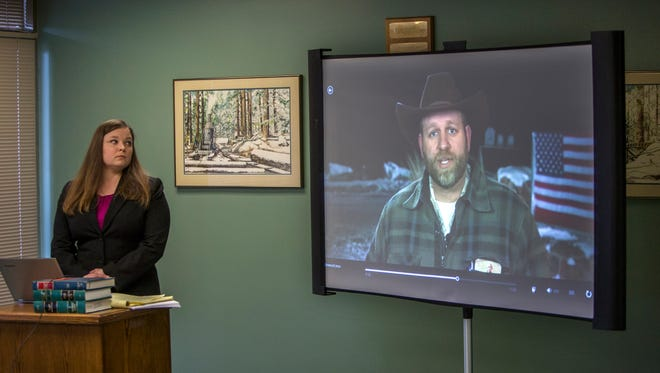 Attorney Lissa Casey, attorney for Ammon Bundy, listens to a recorded statement by Bundy as an image of him is shown on a screen, in Eugene, Ore., on Thursday, Feb. 4, 2016. The statement was recorded during a telephone conversation between Bundy and his attorneys, Casey and Mike Arnold, from the Multnomah County Jail. Authorities arrested Bundy, the leader of an armed group occupying Malheur National Wildlife Refuge and others on a remote road when they left  the Oregon refuge for a community meeting.
