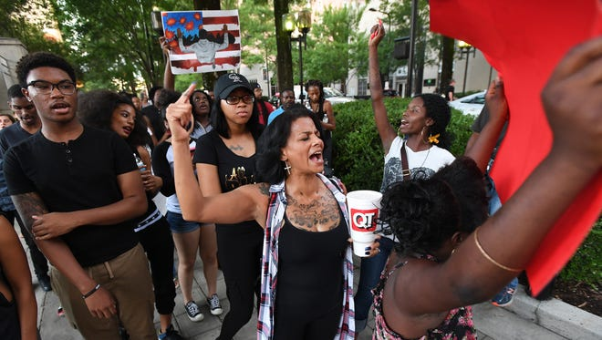 Laura Holder leads a chant as a group of around 50 protesters walk up Main Street during a Black Lives Matter rally in downtown Greenville on July 11, 2016.