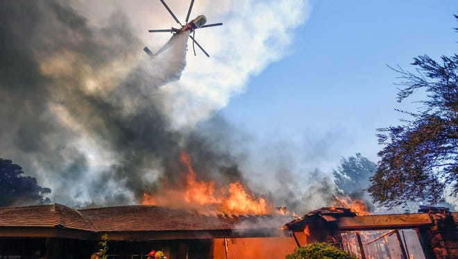 A helicopter dumps water on a home as firefighters battle a wildfire in Anaheim Hills in Anaheim, Calif.