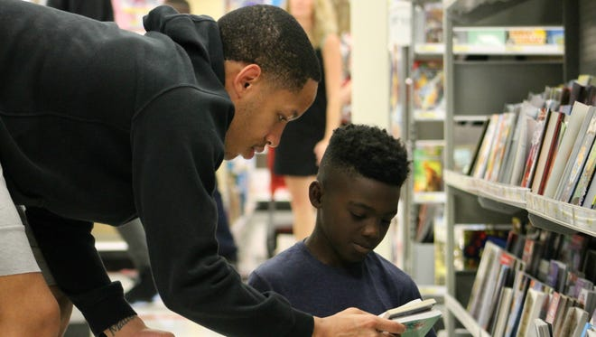 FSU guard CJ Walker looks at books with 9-year-old Timarrie Stebbins while on a Christmas shopping spree at Target.