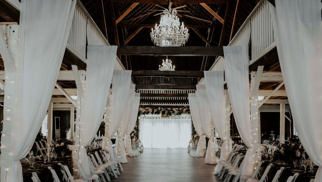 Drapes, string lights, chairs and tables are set out below The Loft on Isanogel's two sparkling chandeliers for the venue's first wedding in November 2017.