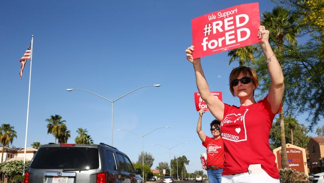 Bonnie Walker, a teacher from Tarwater Elementary in Chandler joins another Arizona teachers in protest along Baseline Road on Apr. 25, 2018 in Mesa, Ariz., on the eve of a planned walkout on April 26, for higher pay and more education funding.