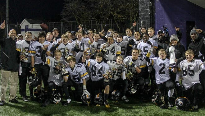 Members of the Plymouth-Canton Steelers varsity football team pose with their Super Bowl trophies Saturday night.