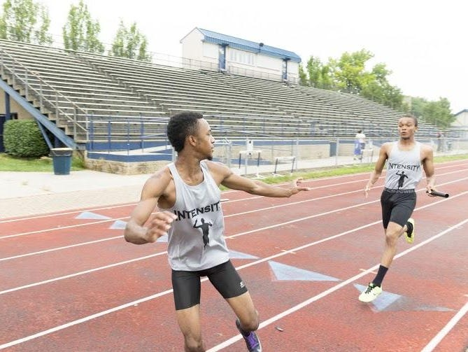 Perfecting their baton handoffs are Intensity relay team members Montel Hood (foreground) and Malik Jordan.
