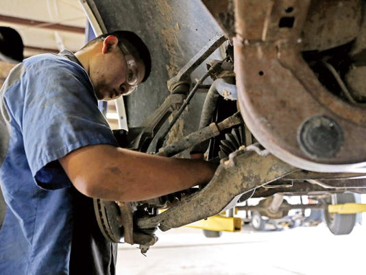 Auto technician Michael Betsuie replaces the shocks on a customer's pickup truck on Monday at Four States Tire and Service on East Main Street in Farmington. The shop's general manager, Matt Messier, said residents should consider bringing in their cars between now and Christmas to get them winterized. He said residents can do three main things to prepare for winter: replace the tires and brakes and align their car's wheels.