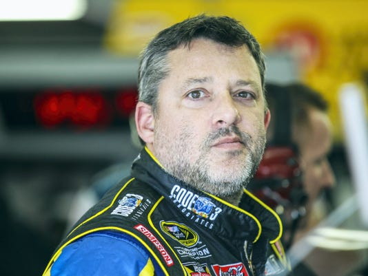 Tony Stewart waits in the garage while his car is worked on at New Hampshire Motor Speedway.