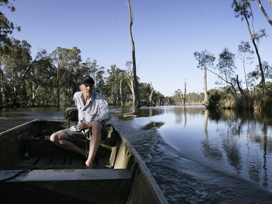 Aussie Phil Tripp maneuvers his boat down the Murray River in Victoria, Australia. The river is the main source of water for the region, much like the Rio Grande in the Southwest.