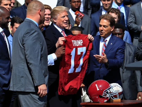 President Donald Trump holds up a team jersey presented