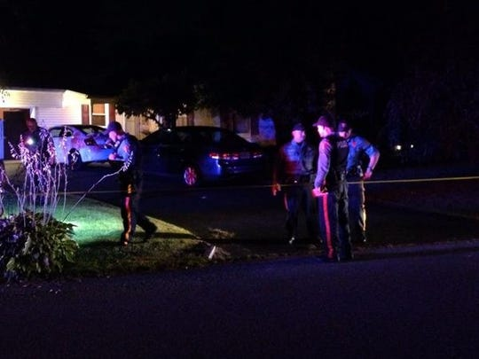 Police search for casings and other evidence on Saturday night along Edna Drive.