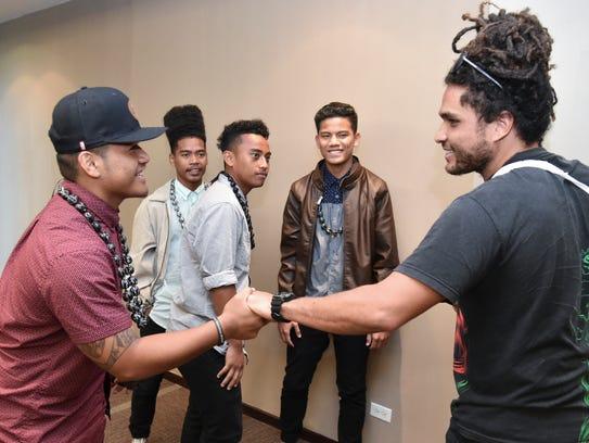 Reggae artist Conkarah, from Jamaica, right, greets