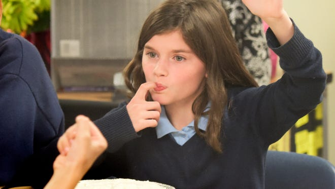 York Academy fifth-grader Helena Lyons licks her finger after frosting a cake as a reward in the Positive Behavioral Interventions and Supports Program on Friday, Sept. 30, 2016. Individual students and entire classrooms earn credits for positive behaviors in the program. The class won the sweet-making after completing a thematic unit on science. They got to eat the cakes they decorated as plant and animal cells. Bill Kalina photo