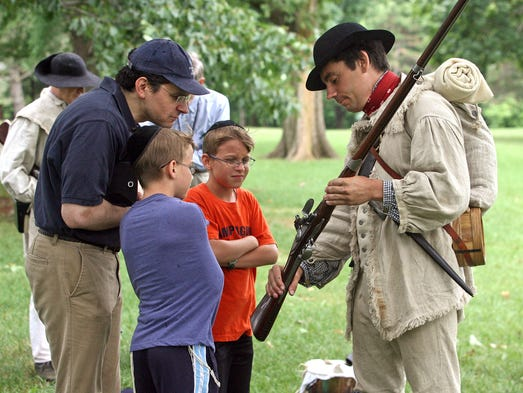 Re-enactors portraying members of the 2nd New Jersey Regiment appear at Buccleuch Park for celebration of the 1776 signing of the Declaration of Independence and the June 1778 American Army victory at the Battle of Monmouth. Re-enactor Pete Michel of Jackson, shows a family his musket. Moshe Heching of Clifton is joined by his ten-year-old twins Chaggai, second from left, and Amos, July 04 2014. New Brunswick NJ. photo by Kathy Johnson EST 0705 Fourth in New Brunswick