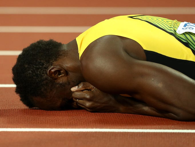 Usain Bolt of Jamaica falls to the track in the 4x100