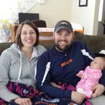 Brenda Burns, left, and her husband, Joshua Burns, pose with their daughter, Naomi Burns, now 1, in this undated family photograph.