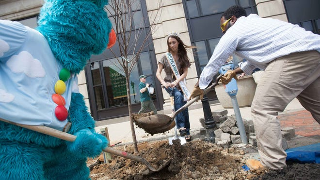 City of Wilmington urban forest administrator Herb White, Miss Delaware U.S. International Danielle Alura and Tropo help plant a tree Wednesday during an Earth Day celebration in Rodney Square in Wilmington.