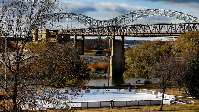 "Workers assemble the city's new ""Fourth Bluff Ice Rink."" Opening this Saturday at Mississippi River Park, the rink will offer family fun under the gaze of the Hernando de Soto Bridge."
