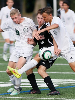 Ridge players Gabe Jeffries (19), left, and Thomas Mazumder (18), right, squeeze out Hunterdon Central's Evan Youshock (16) in Bernards on September 8, 2016.