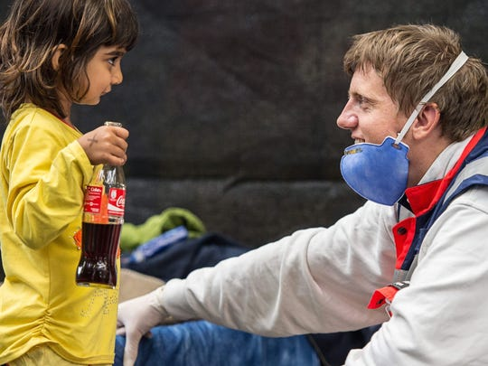 A volunteer from the German Red Cross plays with Zena, a little girl from Syria, in an emergency shelter in Rottenburg, Germany in 2015.