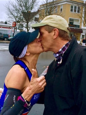 In this April 20, 2015 photo provided by Paige Tatge, her mother, Barbara Tatge, left, kisses an unknown spectator in Wellesley, Mass., as she ran in the Boston Marathon. It's a tradition for male runners to kiss the women attending Wellesley College as they line the marathon route. Barbara made good on a dare by her daughter, Paige, that she kiss a man as she ran along the route. Now they would like to know who she actually kissed. (Paige Tatge via AP)
