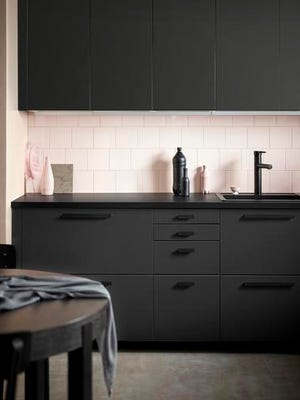 This undated photo provided by Ikea shows kitchen cabinets by Ikea product developer Anna Granath, in collaboration with Stockholm-based studio Form Us With Love, who came up with a new material for kitchen cabinet doors made from processed plastic bottles, and the door itself is made of recycled shredded wood. A rich matte, charcoal-hued finish belies the modest price of the Kungsbacka cabinetry. Designers and manufacturers are finding creative ways to recycle waste products and castoffs.