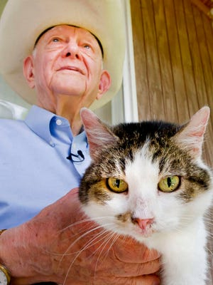 """In this undated photo, Duane Kraemer poses for a photo with  CC, also known as Copy Cat, in rural Brazos County, Texas. CC, the world's first cloned cat, is now 15 years old and lives in what longtime Texas A&M Veterinary Medicine and Biomedical Science researcher Kraemer describes affectionately as a """"kitty barn."""""""