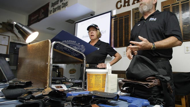 Bill Schmitz (right) and his wife Deb, with D.B.J. LTD CCW Certification of Red Granite, conduct a six-hour class in 2011 to certify people to carry concealed weapons. Proposed legislation would eliminate the training requirement to carry a concealed weapon.