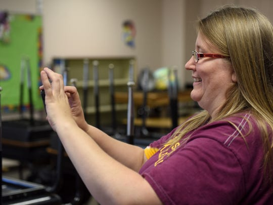 Linda Pinz-Valdez takes photos of the volunteers helping to build a hydroponics system in her classroom at Oscar Howe Elementary on Tuesday. Pinz-Valdez won a $5,000 grant to create a hydroponics system to grow plants during the school year.