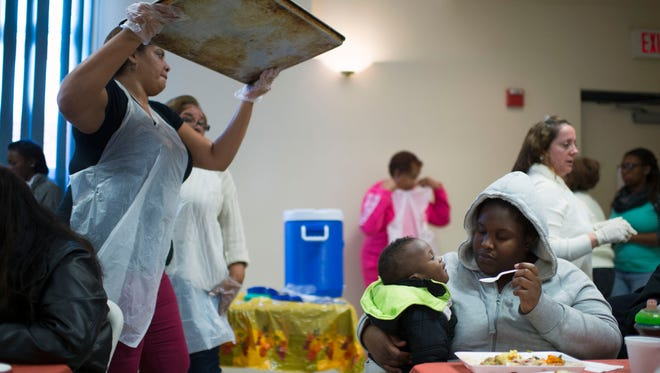 Jenisha Hadden, right, feeds her son Jay'Ceon, 1, as Bethele Development Corp. hosts its annual Thanksgiving Day Grand Celebration Wednesday afternoon, Nov. 25 in Millville.