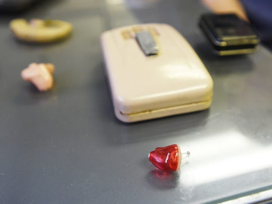 A small, modern hearing aid next to a selection of