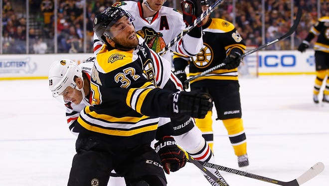 Patrice Bergeron #37 of the Boston Bruins is held while chasing down a puck by Jonathan Toews #19 of the Chicago Blackhawks in the third period during the game at TD Garden.