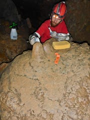 Kevin Strong cleans a floor area in Fort Stanton Cave