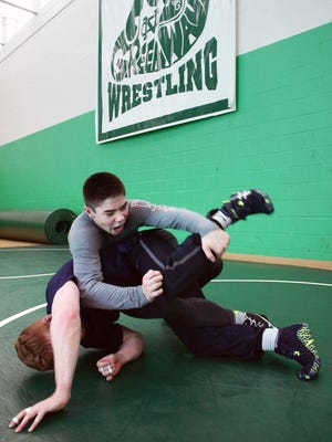 Newark Catholic sophomore Richie Stalnaker spars with Caleb Ohl, a 2014 graduate, Monday after school. Stalnaker qualified for the Division III state meet at 126 pounds.