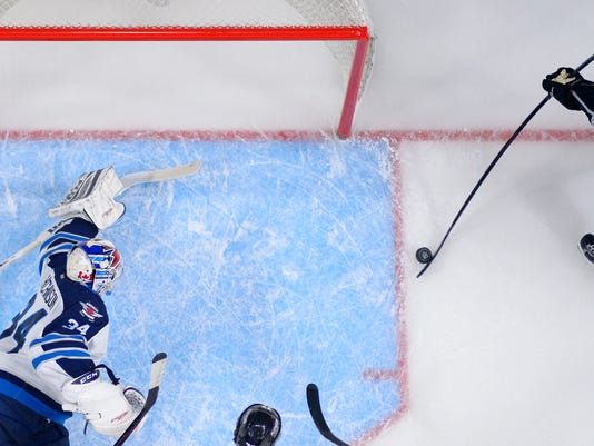 Los Angeles Kings center Anze Kopitar, right, of Slovenia, scores on Winnipeg Jets goalie Michael Hutchinson during the first period of an NHL hockey game, Saturday, Jan. 10, 2015, in Los Angeles.  (AP Photo/Mark J. Terrill)