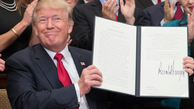 President Donald Trump holds up an executive order on health care after signing it during an Oct. 12 ceremony. The executive order overhauls federal regulations of the health insurance market, encouraging insurance companies to create cheap plans.