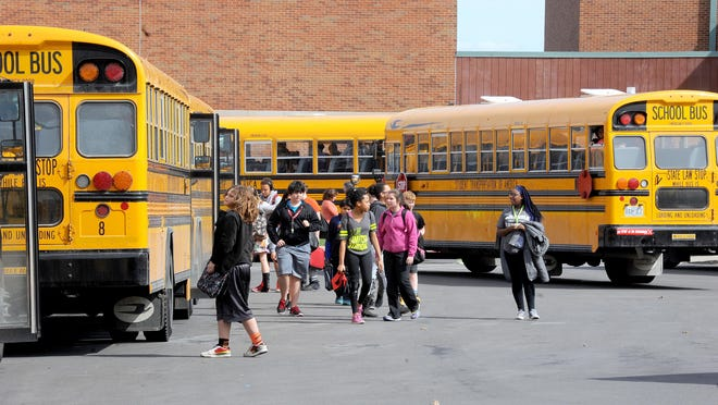 Students at Gentry Middle School board buses after school on March 15, 2016.