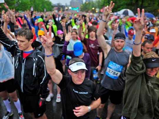 Runners take a moment of silence as they wear blue wrist bands in honor of the Boston Marathon bombing victims at the start line during Country Music Marathon in Nashville, Tenn., Saturday, April 27, 2013.