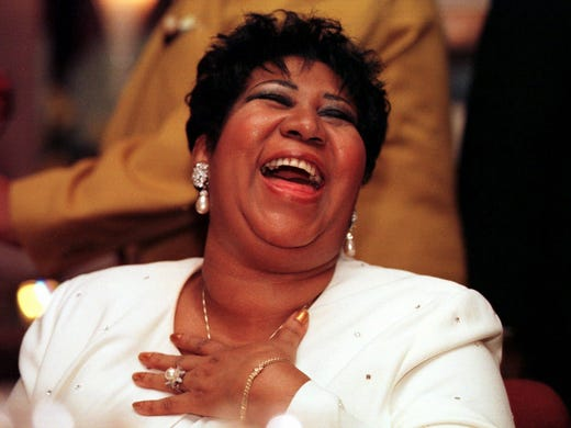 Singer Aretha Franklin leans back in her chair and