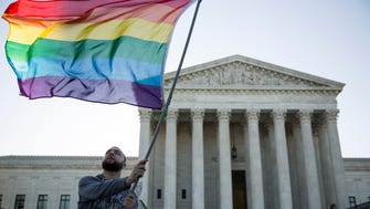 Same-sex marriage supporter Vin Testa, of Washington, D.C., waves a rainbow pride flag in front of the Supreme Court on Tuesday morning.