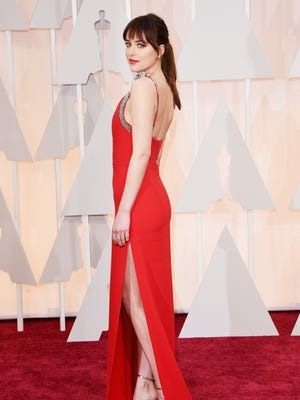 """Dakota Johnson of """"Fifty Shades of Grey"""" shows off her gown on the red carpet Sunday at the 87th Annual Academy Awards in Hollywood."""