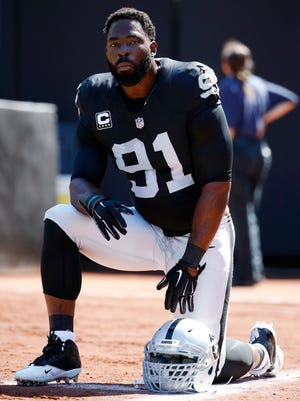 In this Sept. 20, 2015, file photo, Oakland Raiders defensive end Justin Tuck takes a knee during an NFL football game against the Baltimore Ravens in Oakland , Calif. Tuck is retiring after 11 seasons in the NFL. He announced his decision Monday, Feb. 1, 2016, and says he leaves the NFL with very few regrets.