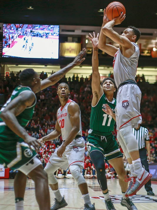 New Mexico's Elijah Brown (4) shoots over the defense of Colorado State's Emmanuel Omogbo, left, and Prentiss Nixion (11) as New Mexico's Sam Logwood (20) watches during the first half of an NCAA college basketball game in Albuquerque, N.M., Tuesday, Feb. 21, 2017. (AP Photo/Juan Antonio Labreche)